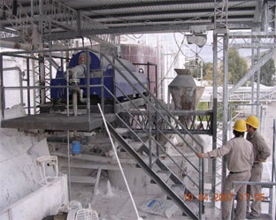 Calcium Carbonate slurry dewatering centrifuge system with hard hat workers looking on